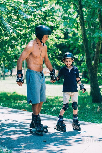 Grandfather and grandson roller skating, holding hands