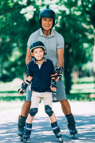 Portrait of grandfather and grandson roller skating in the park
