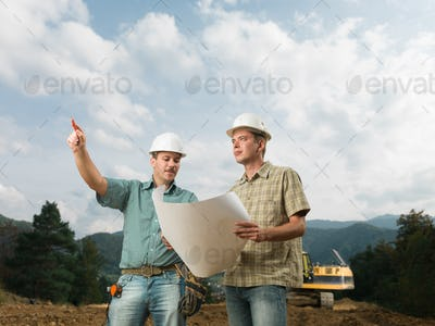 architect and engineer looking at construction blueprint