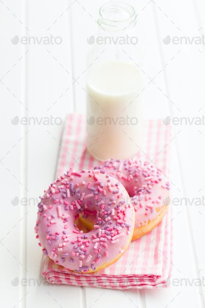 Pink donuts and milk bottle.