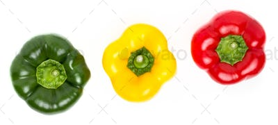 Three peppers of different colors lie in a row on a white backgr