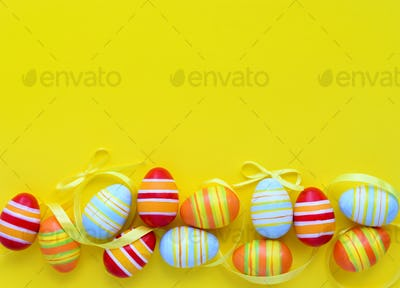 Colorful easter eggs and ribbons on a yellow background with emp