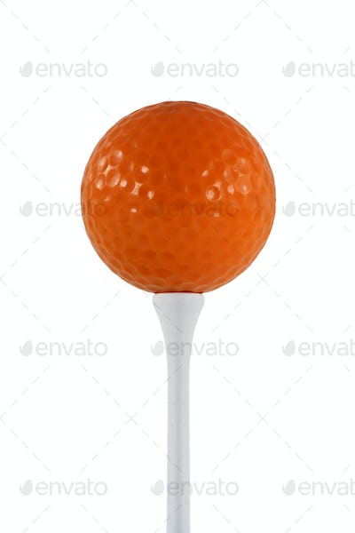 Isolated orange golf ball on a white tee