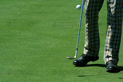 Golfer juggling a golf ball with retro pants
