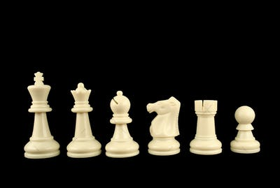 White Chess Pieces on Black Background