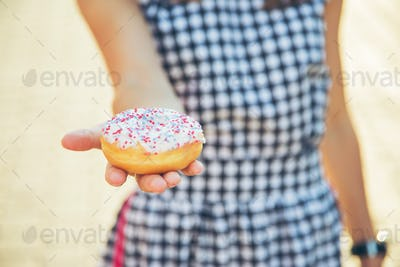Woman holding delicious donut.
