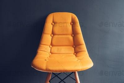 Empty yellow chair against waiting room gray wall