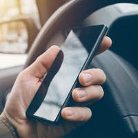 Man driving car and using mobile phone for texting