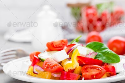 Tomato salad with fresh bell pepper, red onion and feta cheese. Healthy eating
