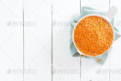 Raw lentil in bowl on table. Fresh lentils. Vegetarian food. White wooden background. Top view