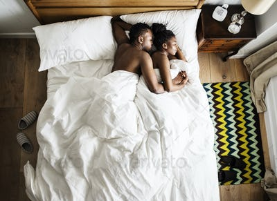 African descent couple sleeping on the bed snuggling and hugging