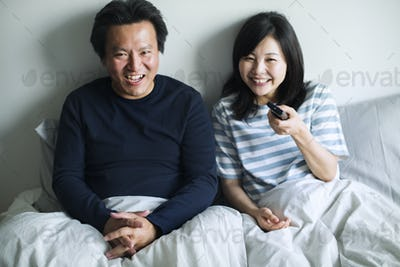 Asian couple watching movie at home together