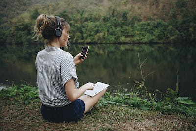 Woman alone in nature listening to music