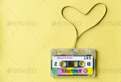 Cassette tape with a heart symbol isolated on yellow background