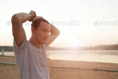 Portrait of athletic positive capoeira man on city beach backgro
