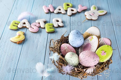 Colorful easter egg end easter cookies as rabbit and egg in the nest on wood background