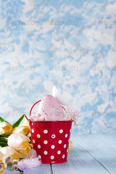 Easter basket filled with colorful eggs on a blue background