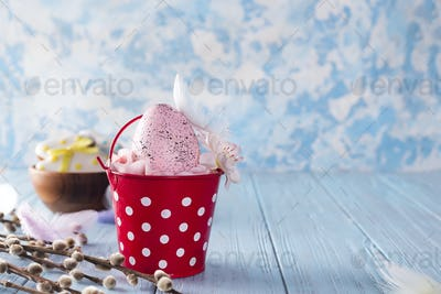 Easter pink Egg in red bucket on a wooden blue background