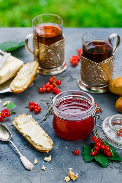 Red currants and jar of jam in garden