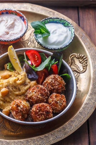 Hummus, falafel, salad in a pan with yoghurt and tahini