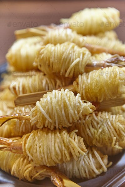 Scampi prawms covered with thin fried potatos. Delicious cuisine. Vertical