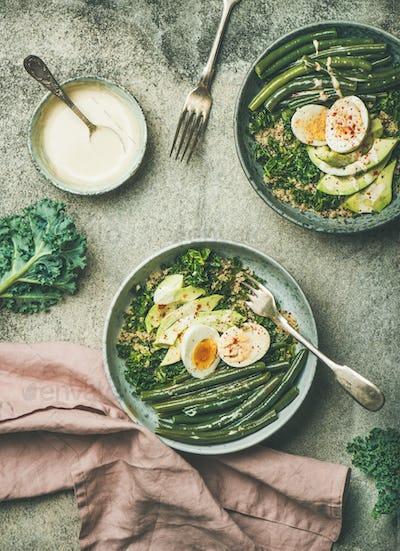 Quinoa, kale, green beans, avocado, egg bowls over concrete background