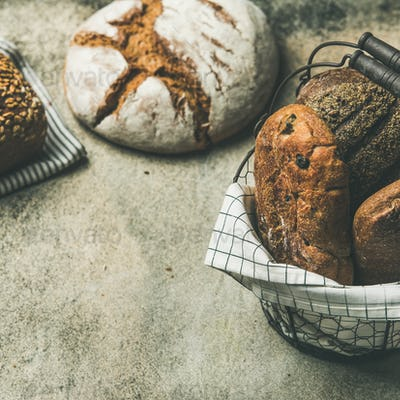 Various bread loaves on grey concrete background, square crop