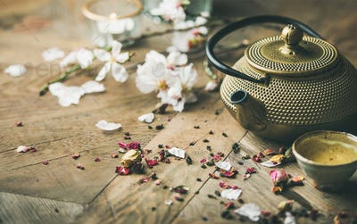 Iron teapot, cups, dried rose buds, blooming almond flowers, candles