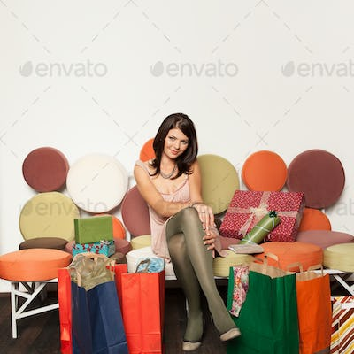 girl sitting on sofa with shopping bags
