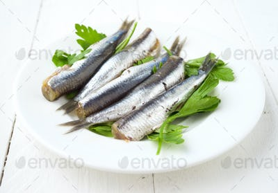 bunch of ordered raw sardines on plate with parsley on wooden