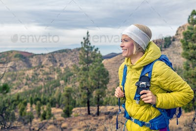 Hiking woman with backpack looking at inspirational mountains la