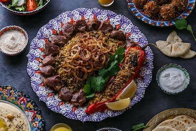 Mejadra or rice with lentils with shish kebab in traditional plate
