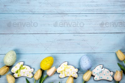 Sweets for celebrate Easter. Gingerbread in shape of easter bunny, colorful eggs and tulips