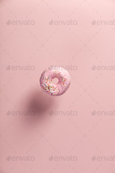 Pink doughnut with sprinkles falling or flying in motion
