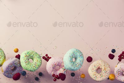Sweet and colourful doughnuts falling or flying in motion