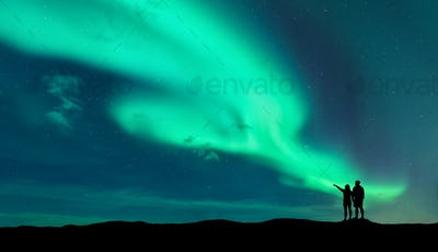 Aurora borealis and silhouette of man and woman
