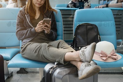 Young asian woman using smart phone at the airport