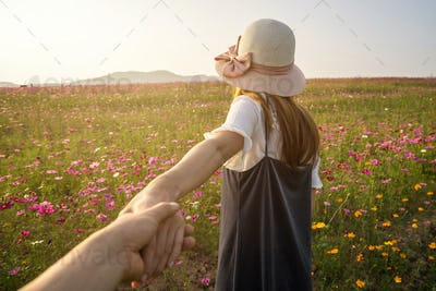 Young woman traveler holding man's hand and leading him