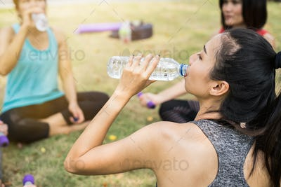 Group of sport women drinking water after workout