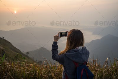 Young traveler taking photo beautiful landscape sunset