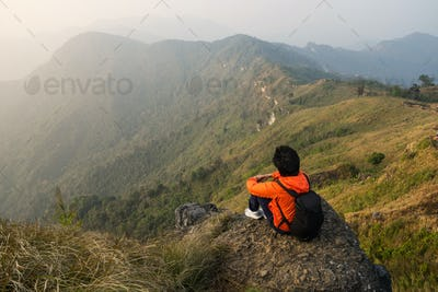Young traveler sitting and looking at beautiful landscape