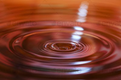 Macro photo of water drops falling into a pool of water
