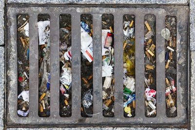 Sewer full of garbage. Urban pollution. Waste treatment. Clean cities