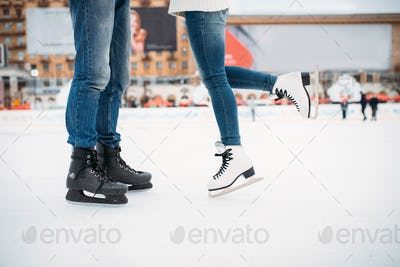 Male and female legs in skates, couple on the rink