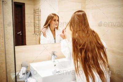 Woman in bathrobe against mirror in bathroom