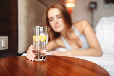 Female hand holds glass with lemon water