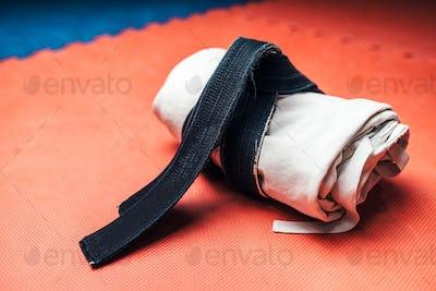 Martial arts, white kimono and black belt closeup