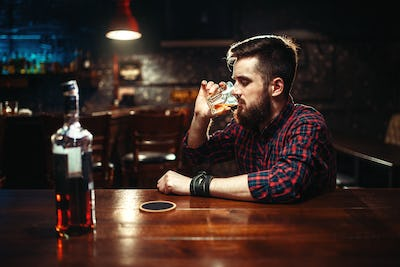 Man sitting at the bar and drink strong alcohol