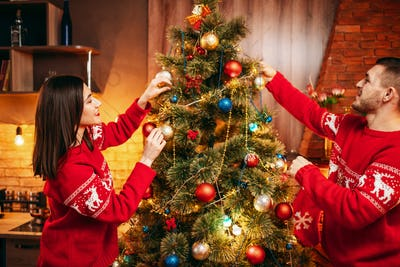 Happy love couple decorate christmas tree