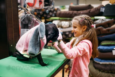 Little girl chooses clothes for puppy in pet shop